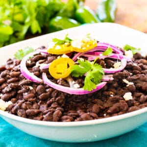 Spicy Black Beans in white bowl, topped with red onion and cilantro.