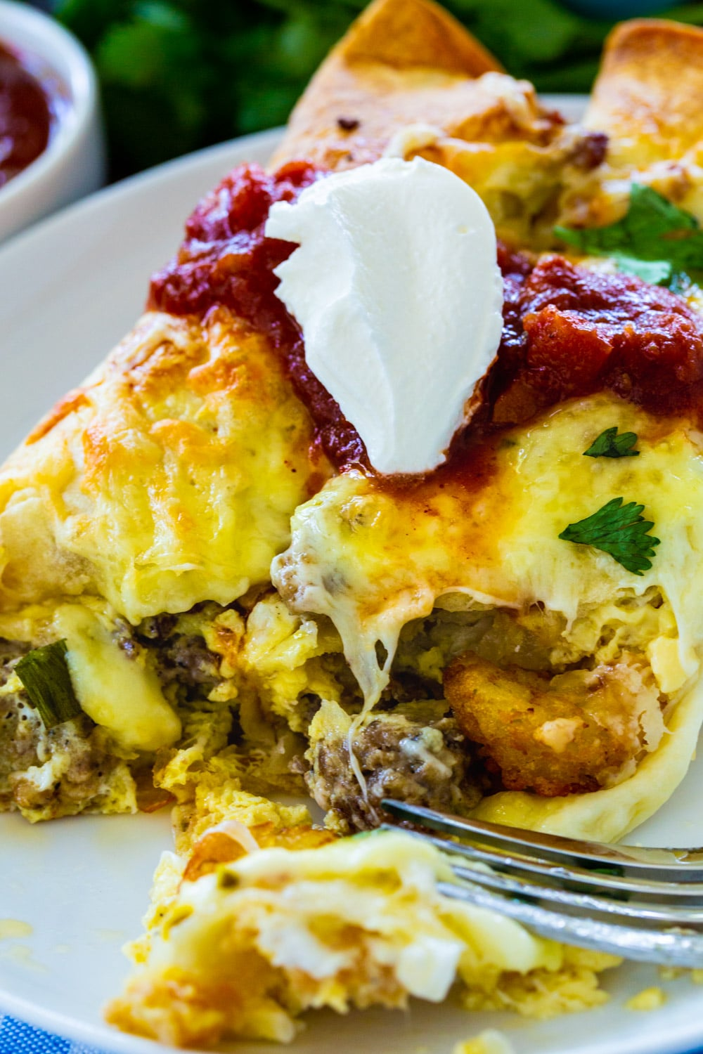 Fork cutting into Spicy Sausage Breakfast Enchilada