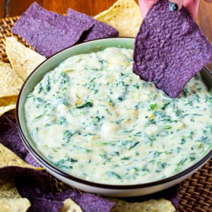 Spinach Artichoke Dip in a bowl with tortilla chips.