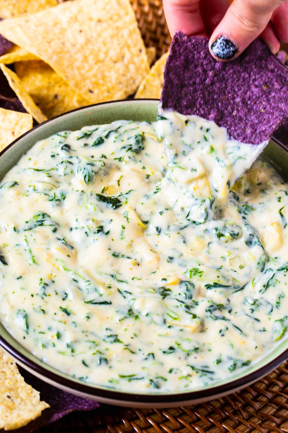 Spinach Dip in a bowl beinf scooped by a tortilla chip.