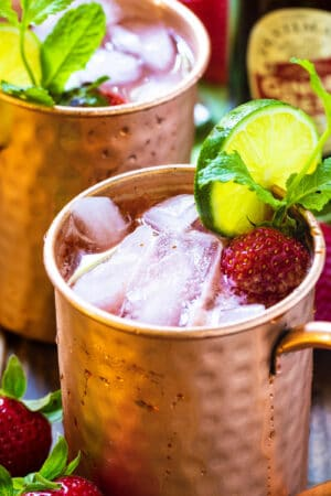 Strawberry Moscow Mule in copper cup with lime and mint.