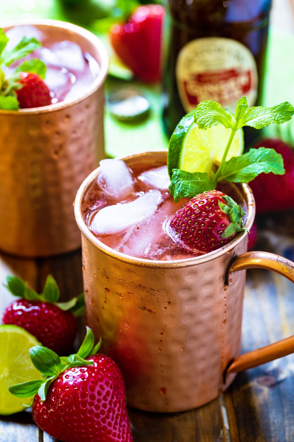 Two Strawberry Moscow Mules with mint and fresh strawberries.