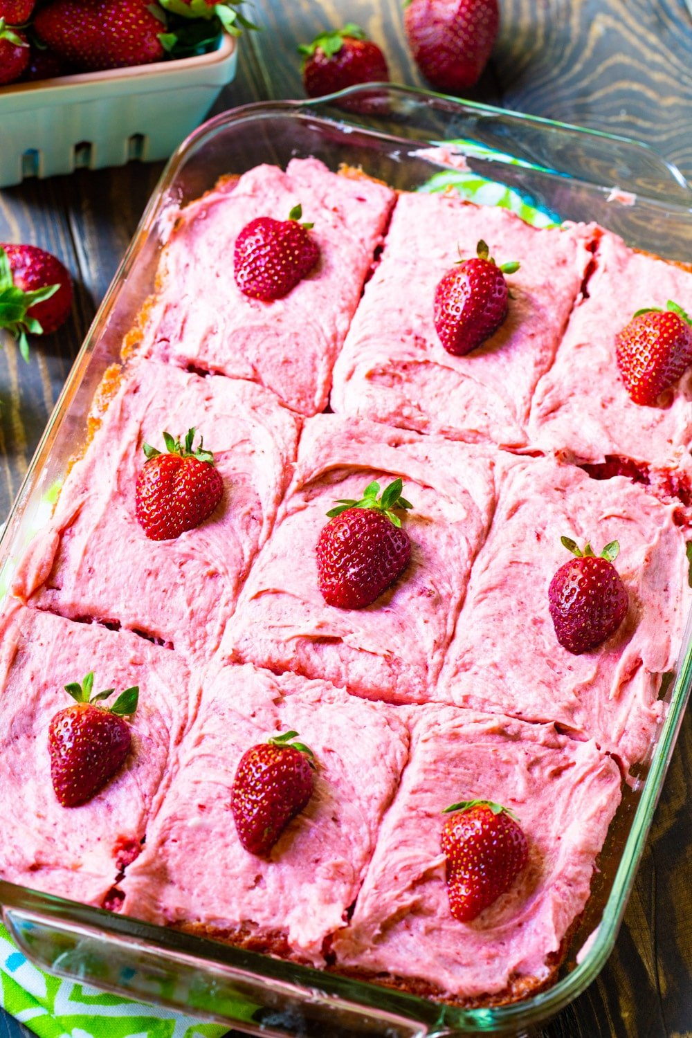 Strawberry flavored sheet cake cut into squares in a baking pan.