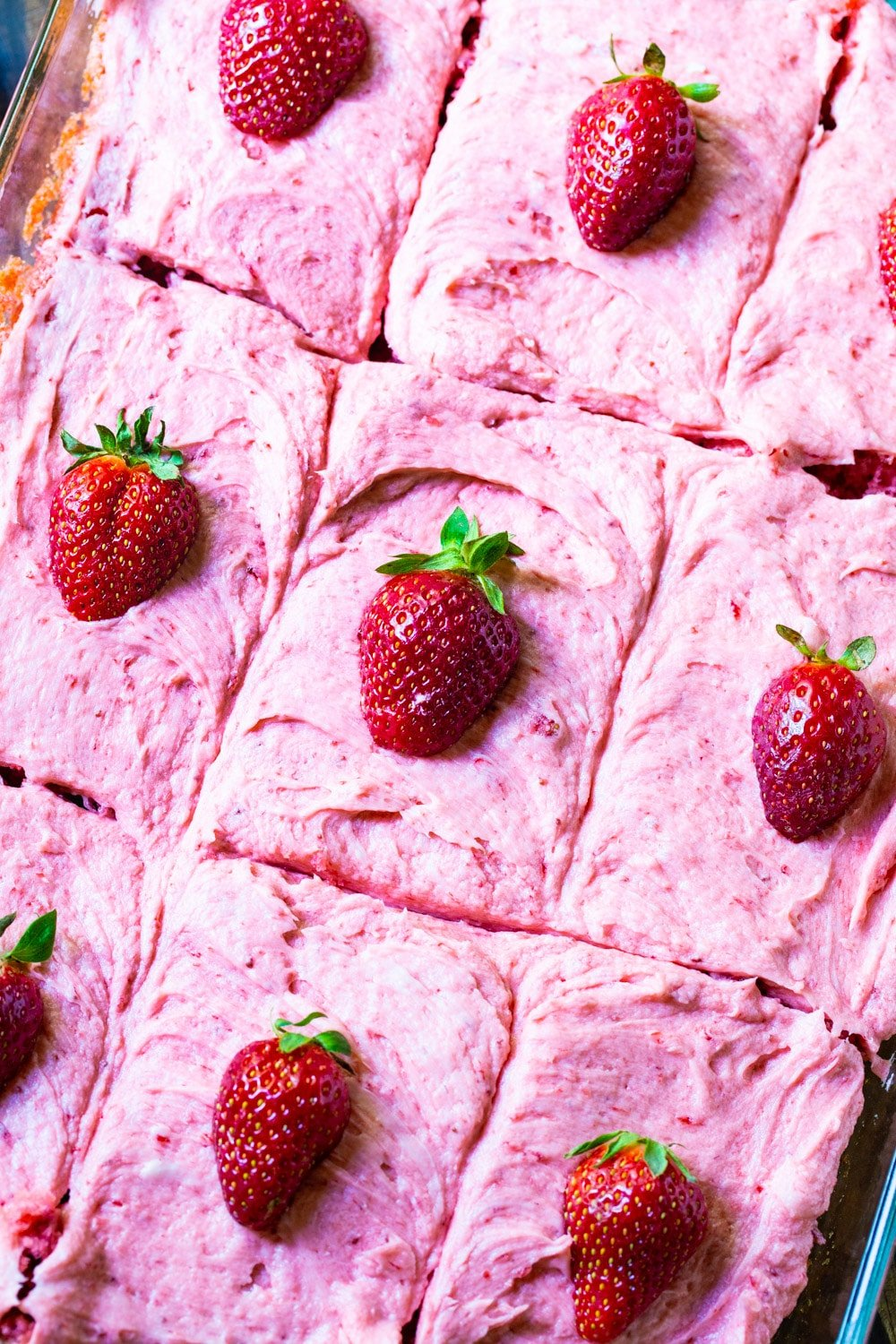 Sheet cake cut into squares in pan. Each one topped with a strawberry.