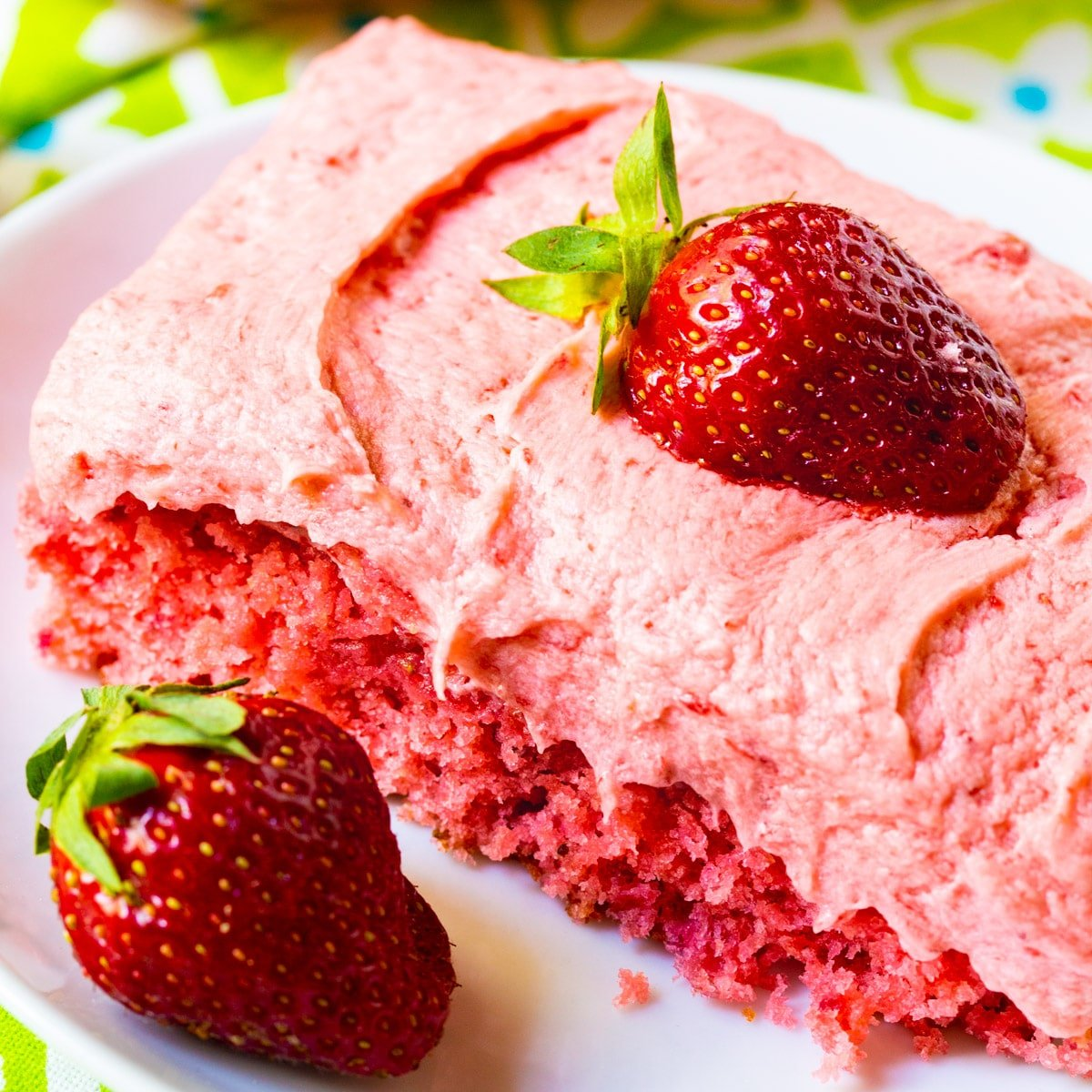 Slice of Strawberry Sheet Cake on a plate with a fresh strawberry.