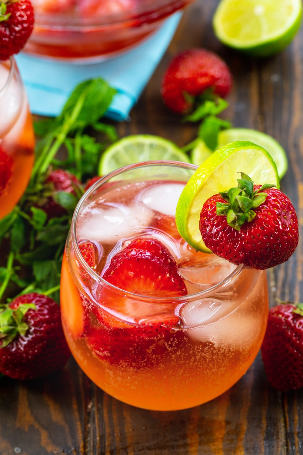 Strawberry Shortcake Sangria in a wine glass with lime slice and fresh strawberry.