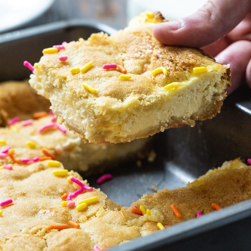 Hand picking up a Sugar Cookie Cheesecake Bars