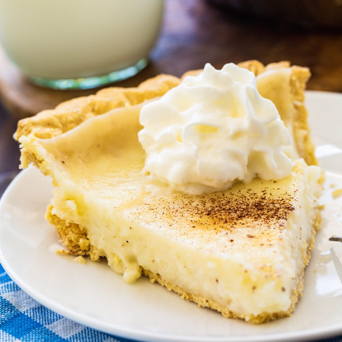 Slice of Sugar Cream Pie topped with whipped cream.