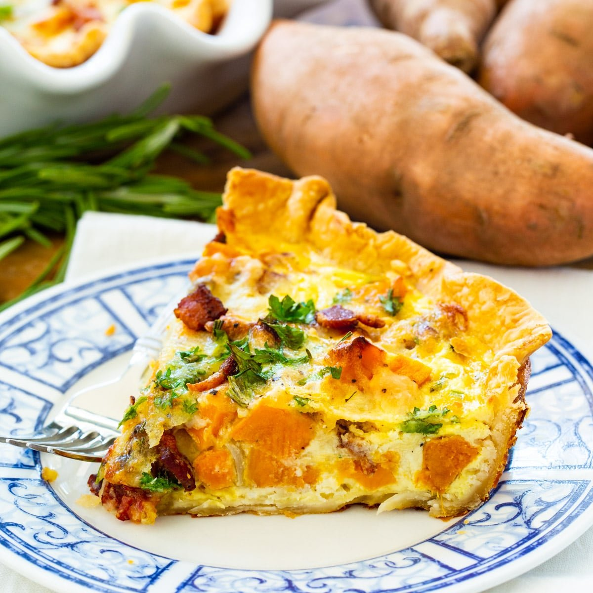Slice of Roasted Sweet Potato Quiche on a plate.