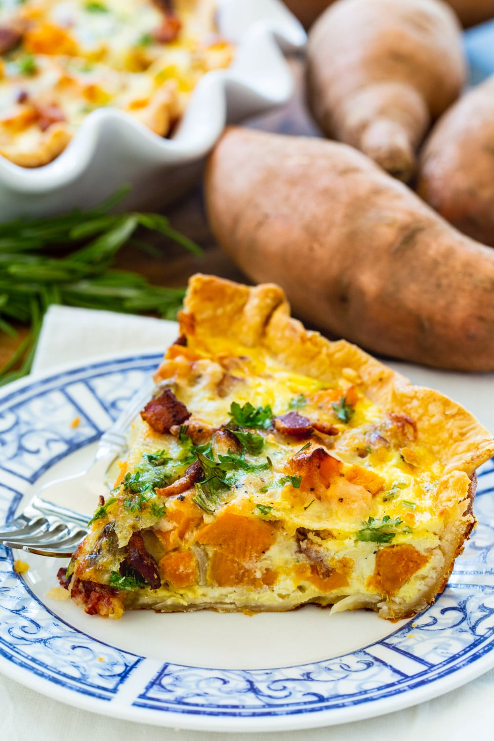 Slice of quiche with roasted sweet potatoes on blue and white plate.