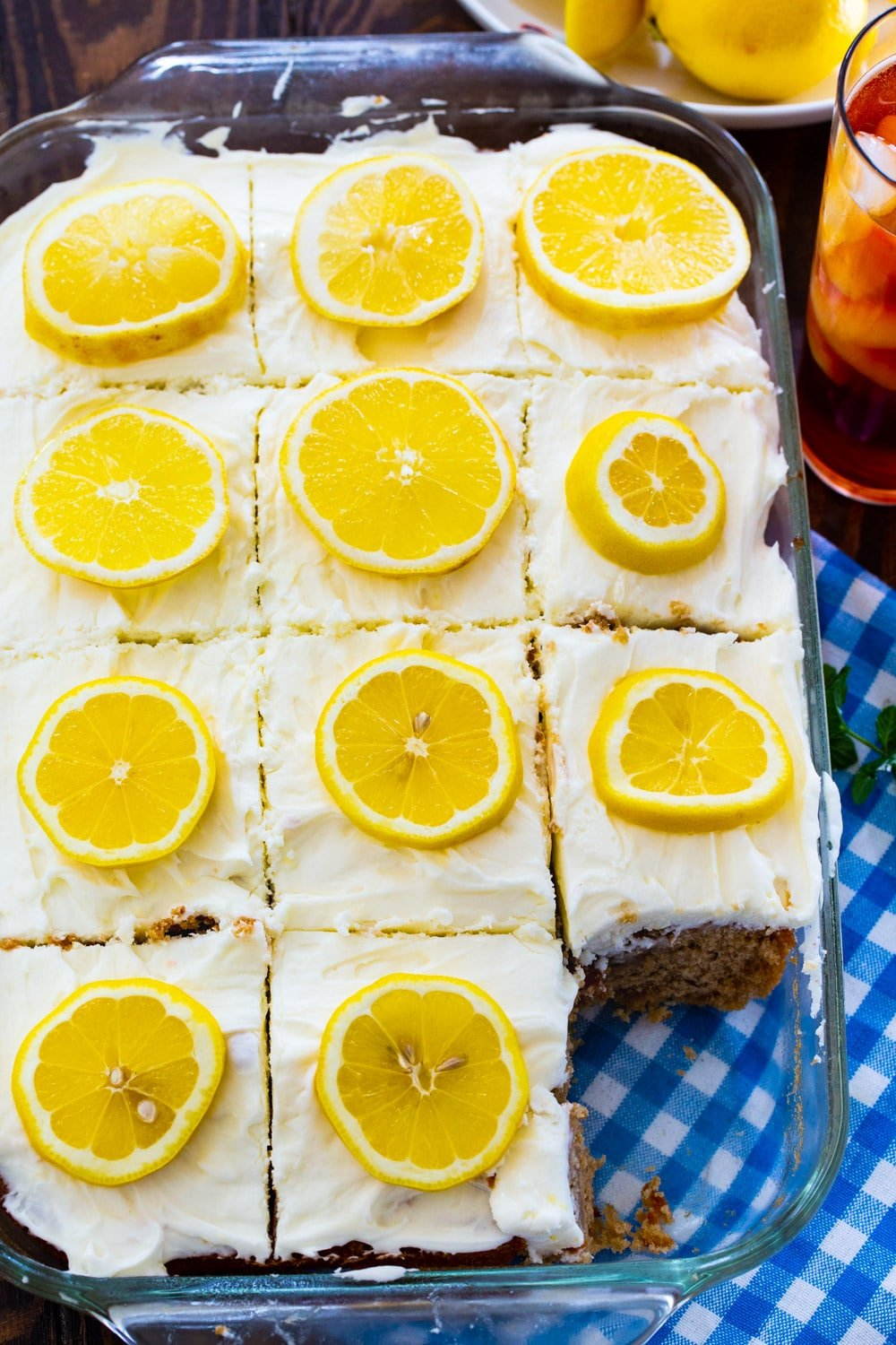 Cake topped with lemon slices in a 9x13-inch pan.