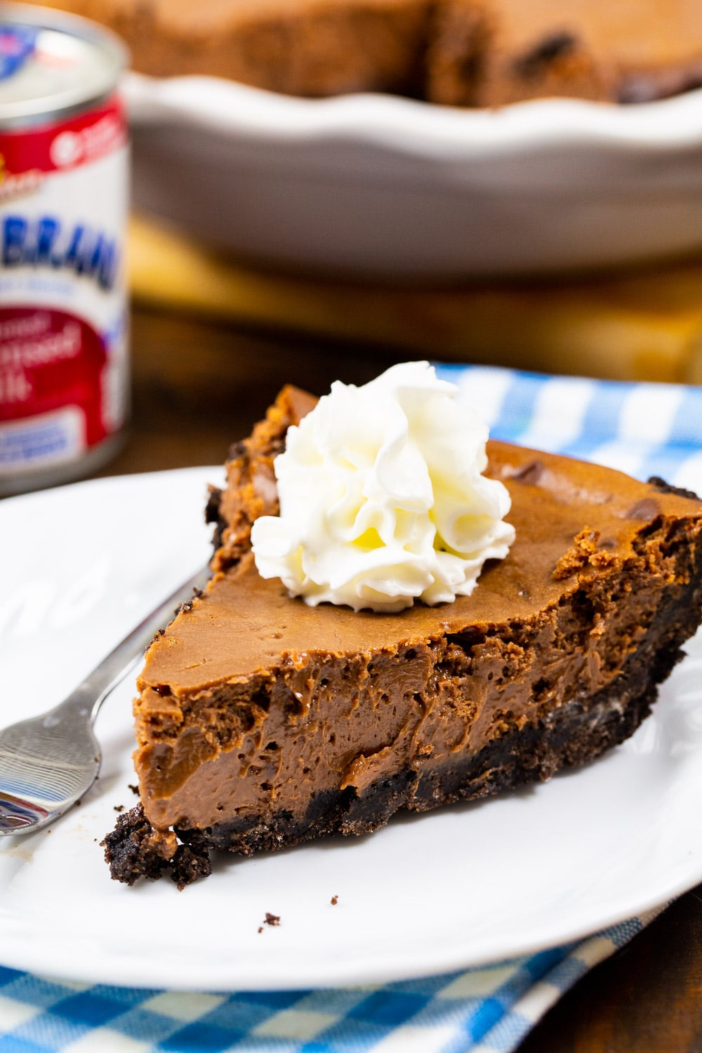 Slice of Sweetened Condensed Milk Chocolate Pie topped with whipped cream.