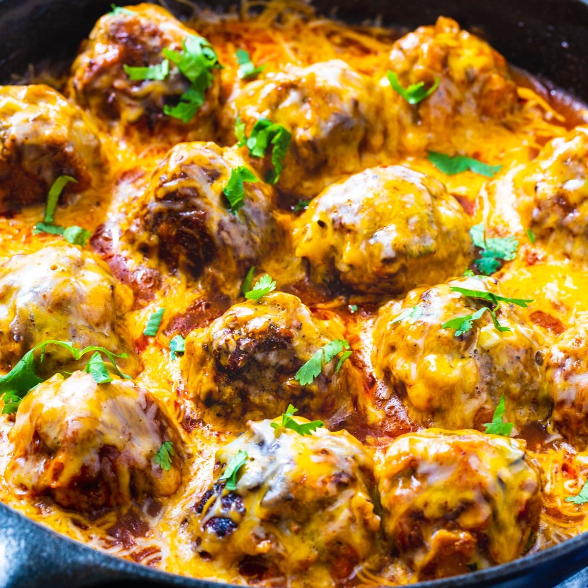 Tex Mex Meatballs coated with cheese in skillet.