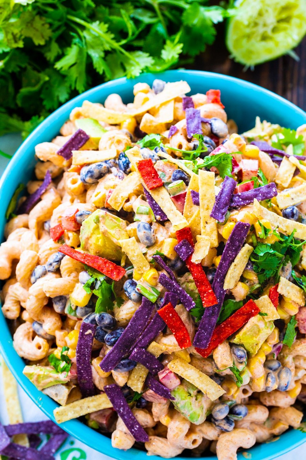 Pasta salad in a blue bowl with bunch of cilantro beside it.