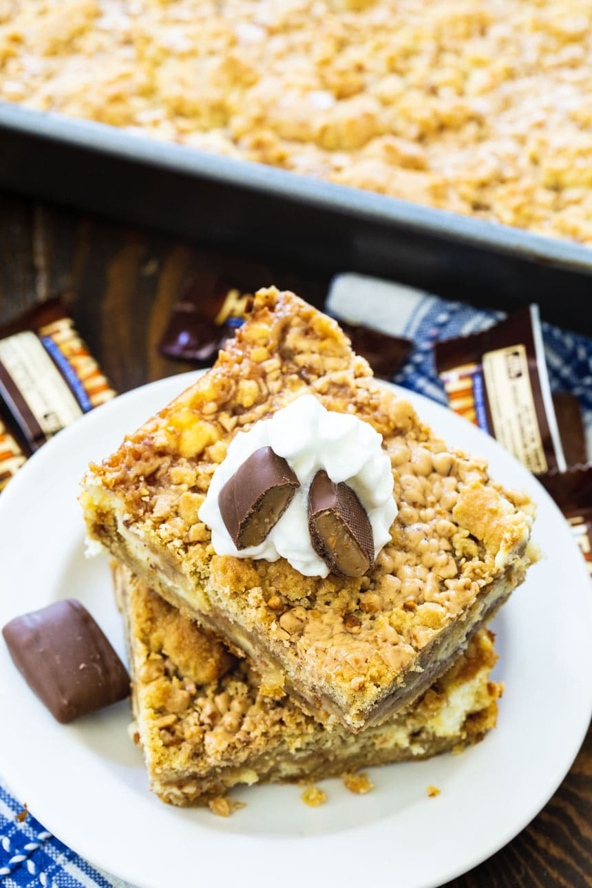 Toffee Cheesecake Bars on a plate with pan full of bars next to them.