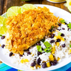Tortilla Crusted Chicken with beans and rice on a white plate.