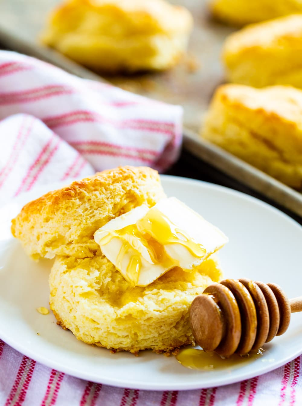 Biscuit split open and covered with butter and honey.