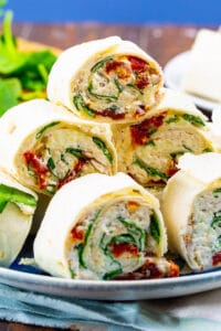 Tuscan Chicken Pinwheels piled up on a plate.