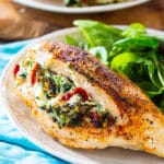 Tuscan Stuffed Chicken on a plate with salad.