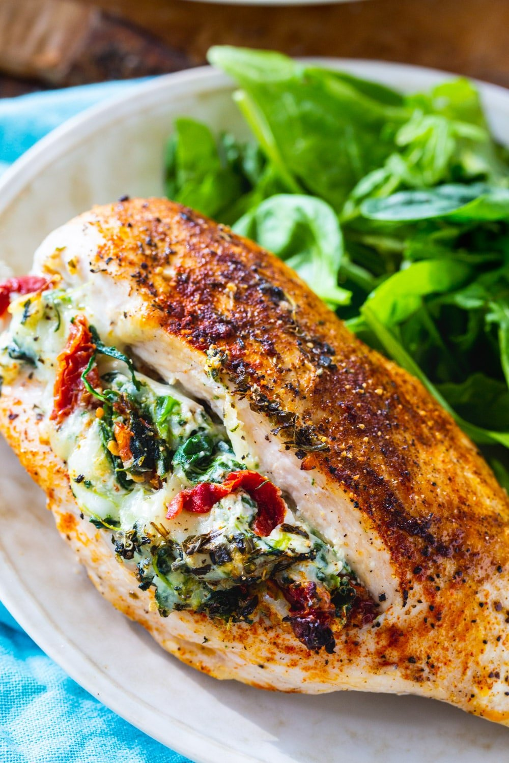 Piece of Tuscan Stuffed Chicken on plate with green salad.