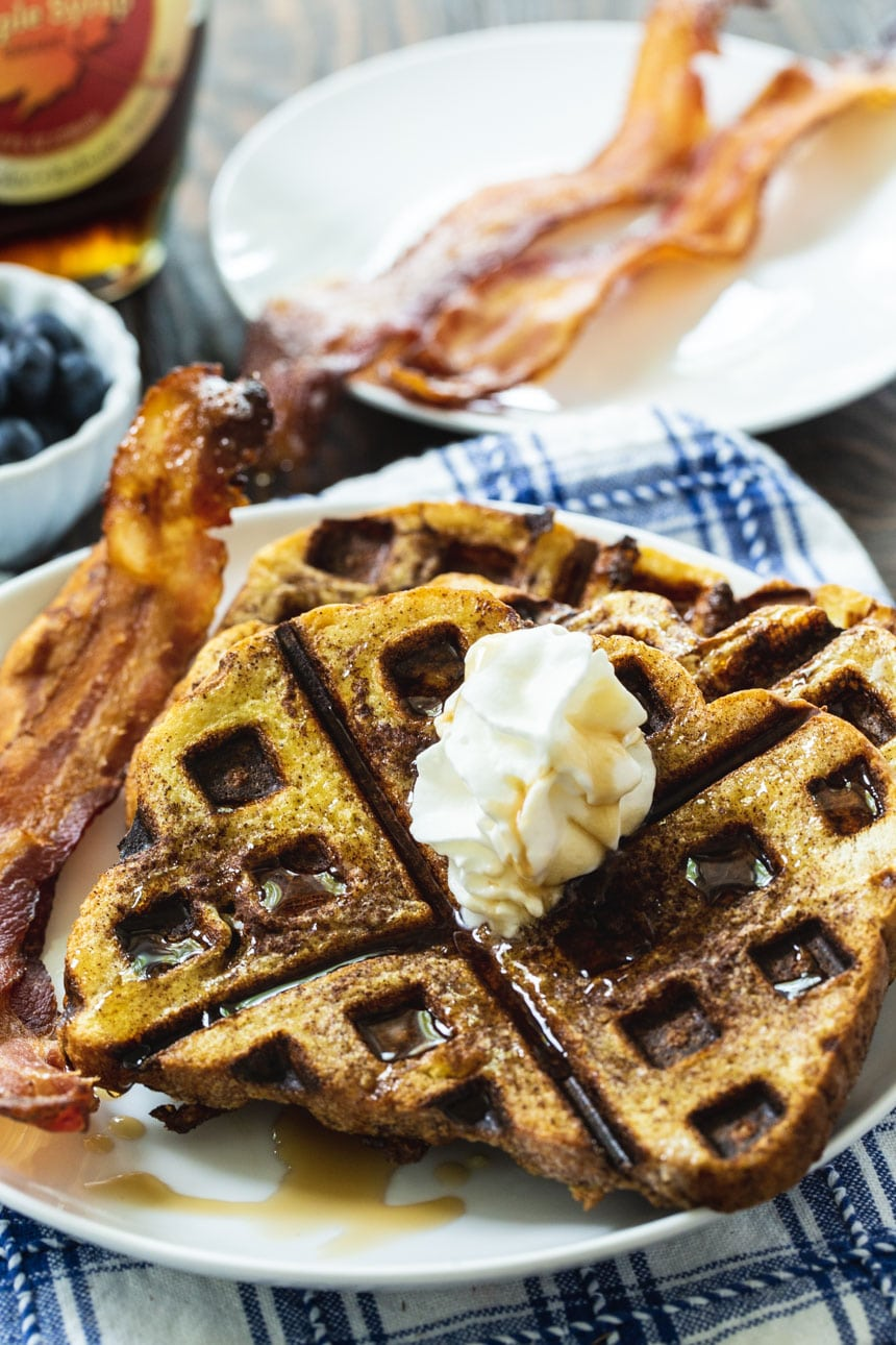 Waffled French Toast on a white plate with plate of bacon in background