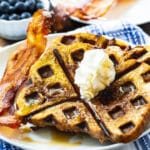 Waffled French Toast on a plate with bacon.