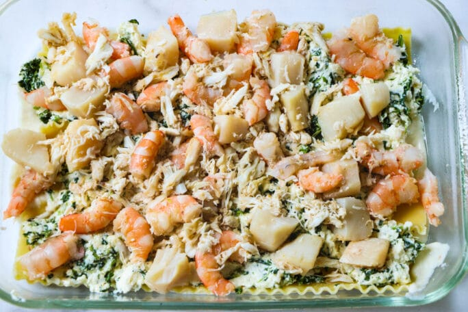Seafood mixture layered on top of ricotta.
