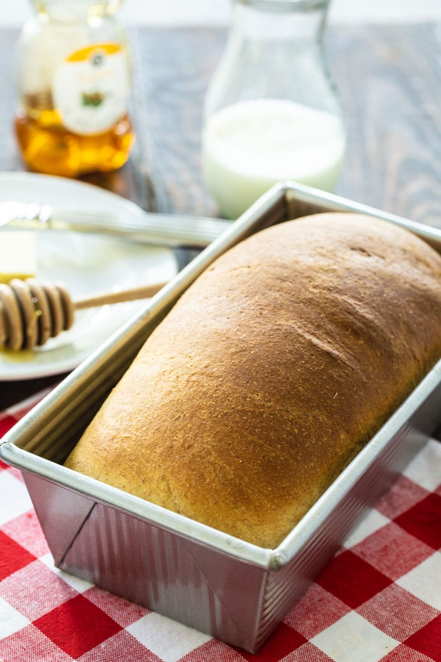 Loaf of Buttermilk Bread in a loaf pan with honey and buttermilk in background.