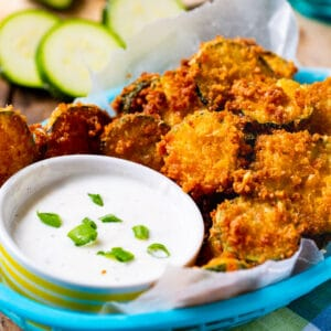 Fried Zucchini Chips with bowl of ranch dressing in a blue basket.