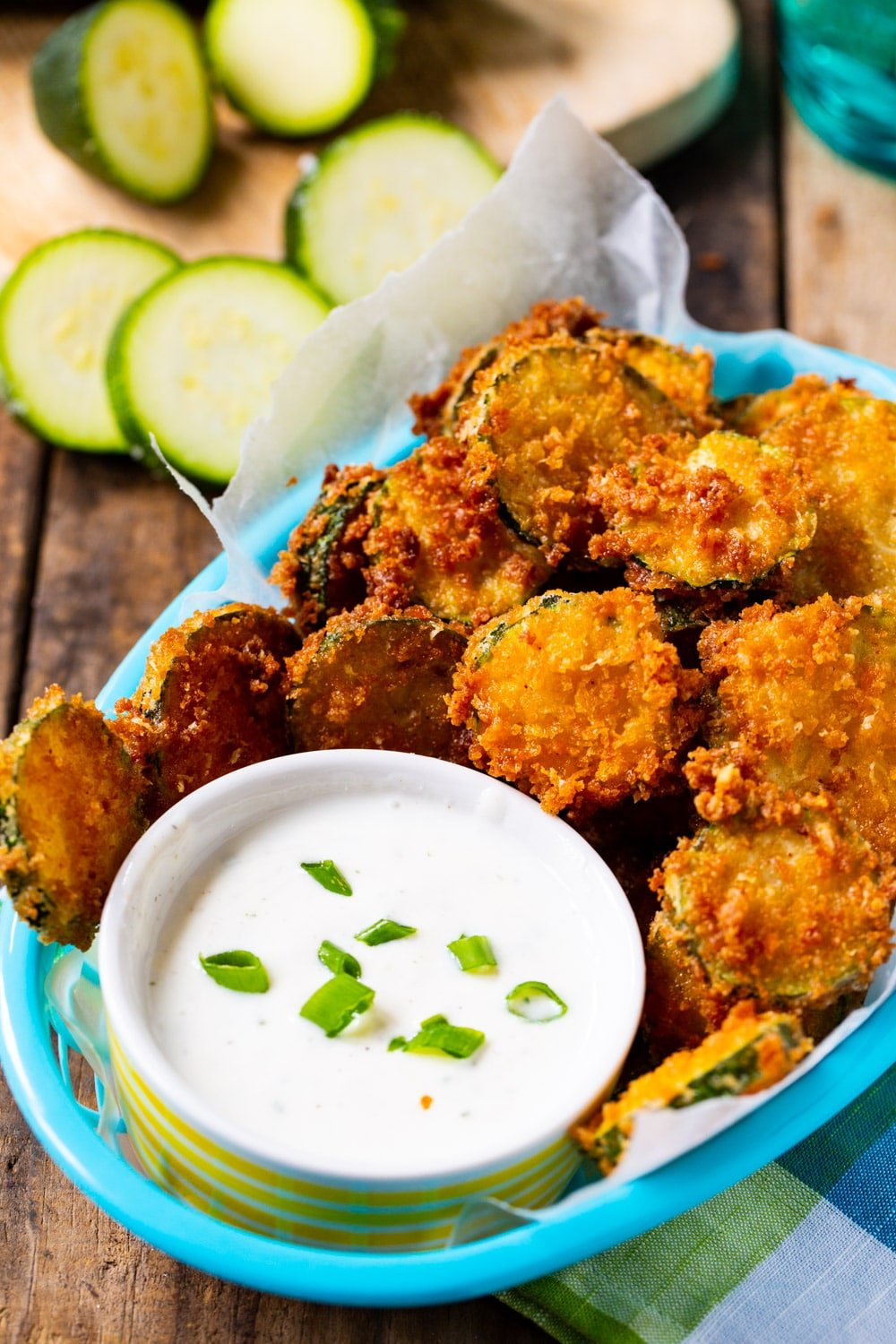 Fried Zucchini Chips in a basket with bowl of ranch dressing.