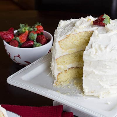 Almond Cake on a cake stand with bowl of strawberries.