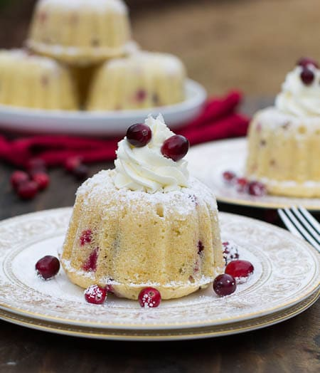 Mini Almond Cranberry Cake topped with  Mascarpone Frosting and decorated with cranberries.
