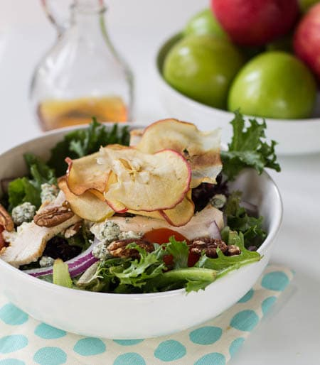 Salad in a bowl with dressing and bowl of apples in background.