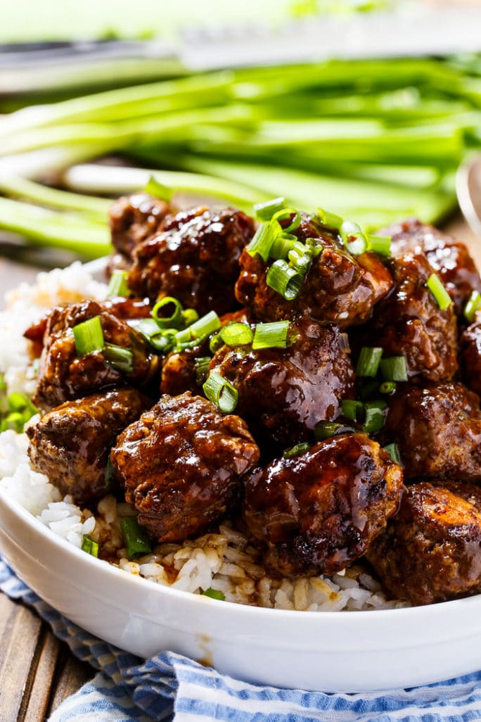 Glazed Meatballs served over white rice in a bowl with green onions in background.