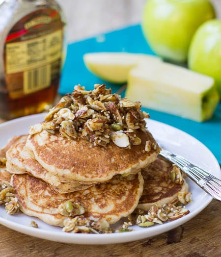 Whole Wheat Apple Pancakes on a plate with yellow apples in background.