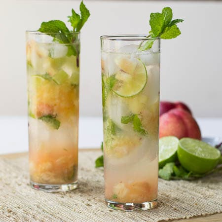 Two Nectarine Mojitos in tall glasses with mint.