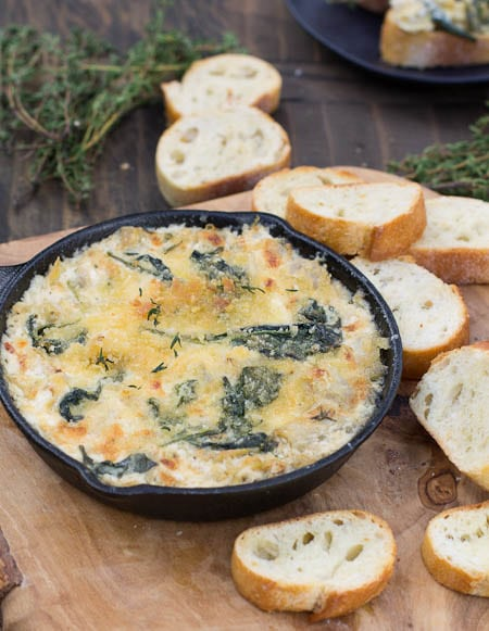 Artichoke Mascarpone Dip surrounded by thyme and baguette slices.