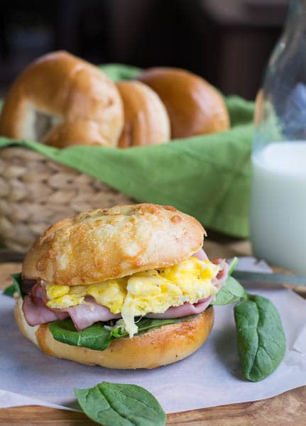 Ham, Egg, and Cheese Bagel Sandwich with bagels in background.