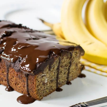 Banana Bread with chocolate glaze dripping down. Bananas in background.