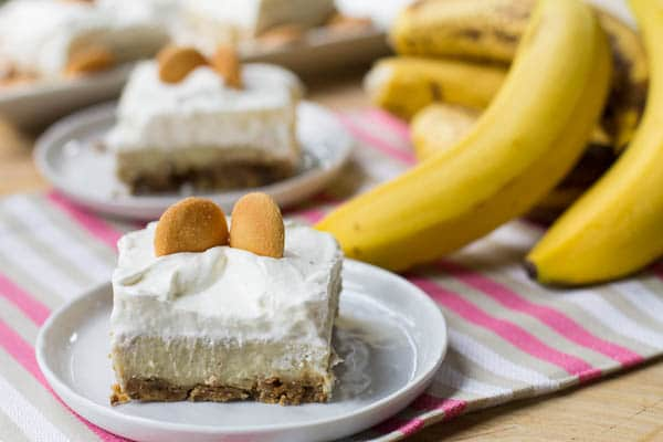 Banana Pudding Bar on a small white plate with bananas in background.