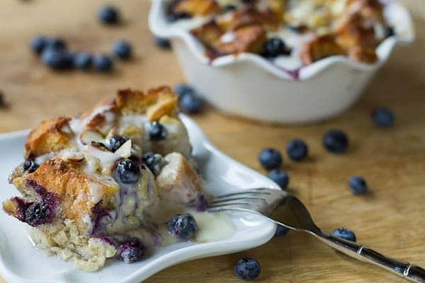 Single serving of Blueberry Bread Pudding with Amaretto Cream on a white plate.