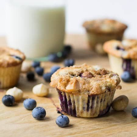 Muffins on a wood cutting board surrounded by fresh blueberries and macadamia nuts.