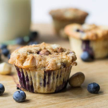 Blueberry Macadamia Muffin with scattered blueberries around it.