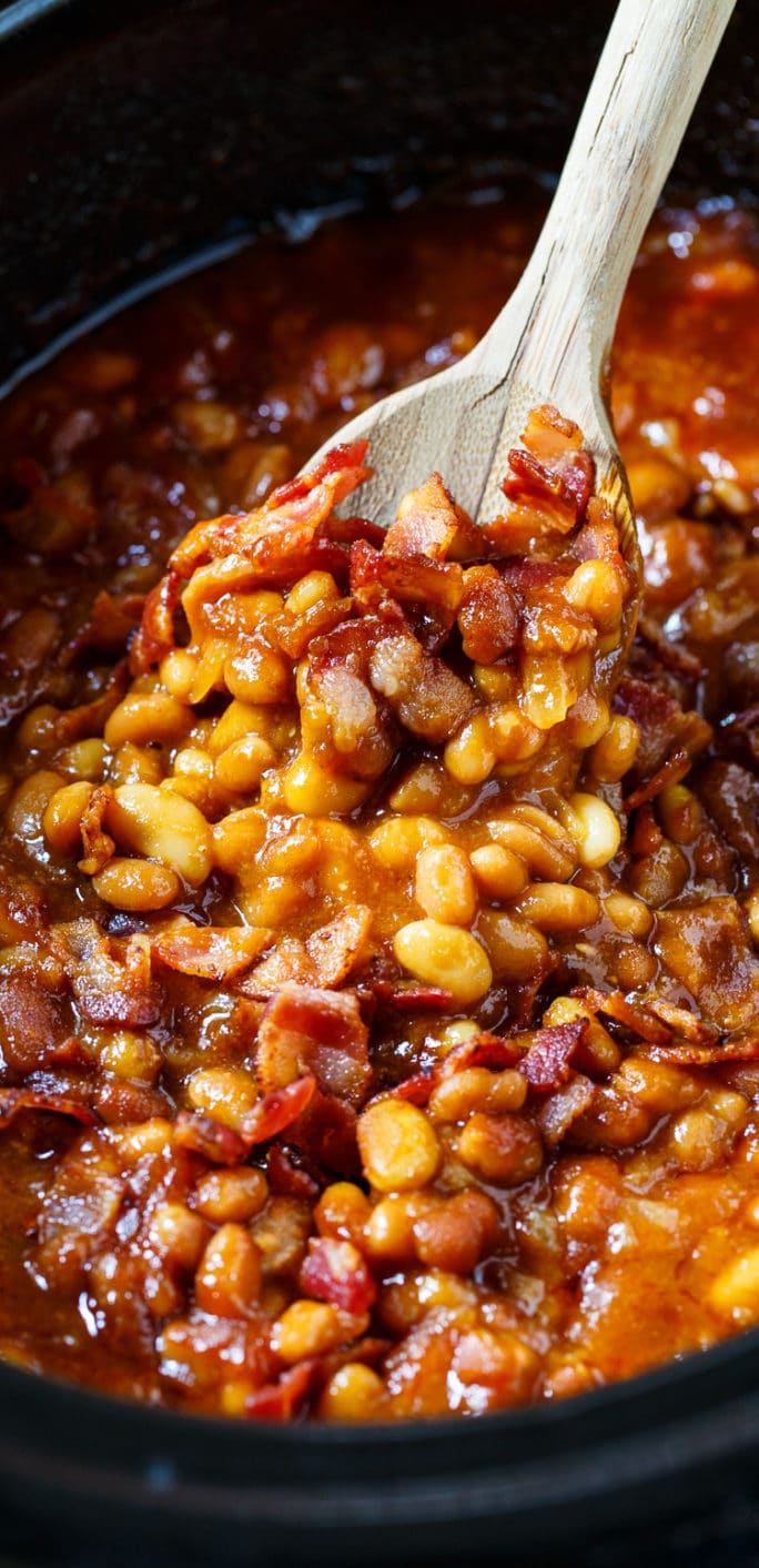 Baked beans in a slow cooker being scooped up with a wooden spoon.