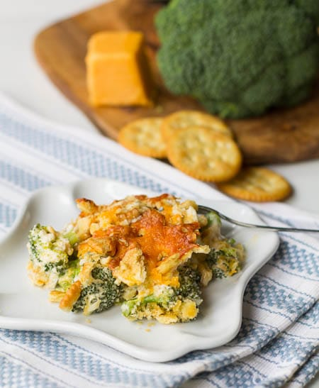 Southern Broccoli Casserole dished up on a small white plate with broccoli and crackers in background.