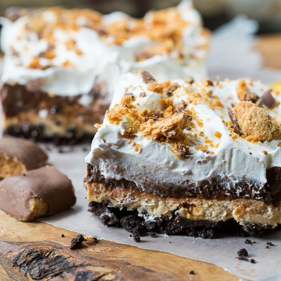 This Butterfinger Chocolate Lush has an oreo cookie crumb crust, a peanut butter layer with crushed butterfingers, a chocolate pudding layer, and Cool Whip on top.