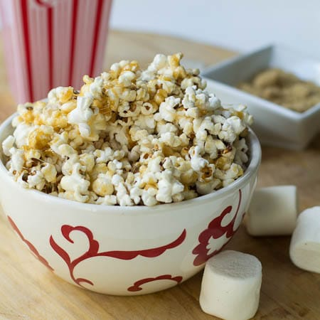 Marshmallow Caramel Popcorn in white and red bowl.