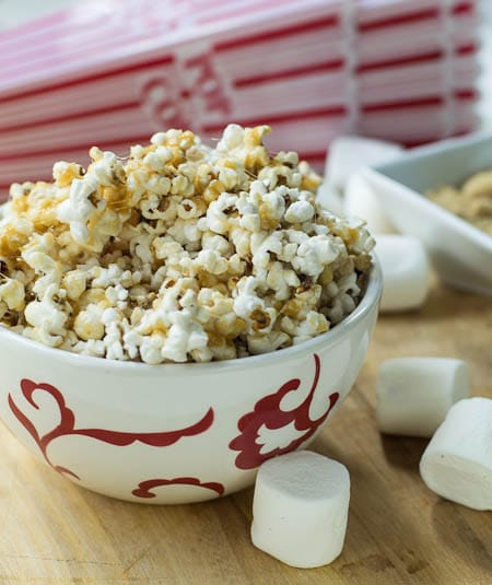 Popcorn in white and red bowl with large marshmallows around it.