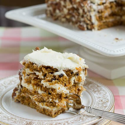 A slice of Carrot Cake on a Plate with a fork stuck in it.