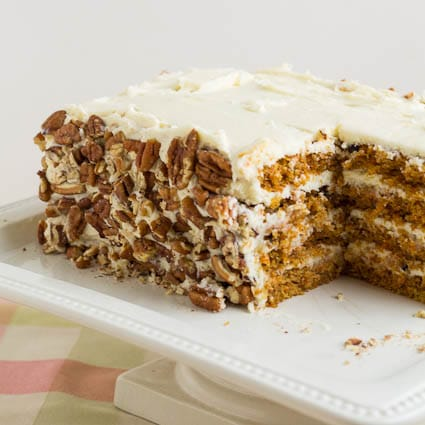 Carrot Cake on a square cake stand with a slice cut out.